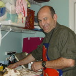 My wonderful husband cutting the turkey, confined to the laundry room because the turkey is so messy, and still smiling away!